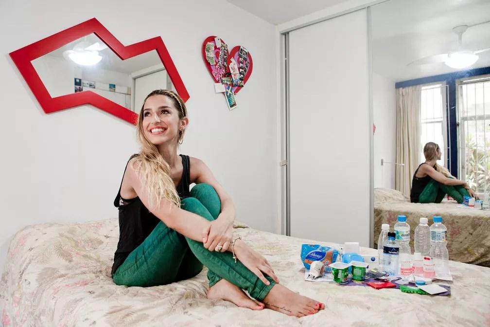 Mulher posa com embalagens de iogurtes, águas e outros resíduos (Foto: Rafael Duarte/G1)