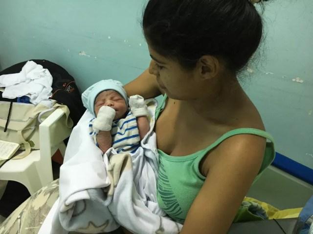 Dagly Monrroy, 24, com o filho, Samtyago Diaz no colo  — Foto: Emily Costa/G1 RR