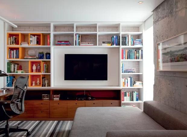 A estante, criada pelo arquiteto Maicon Antoniolli, ganhou caixas cor-de-laranja para a sala/escritório desse apartamento de 96 m² na Vila Olímpia (Foto: Marco Antonio/Editora Globo)