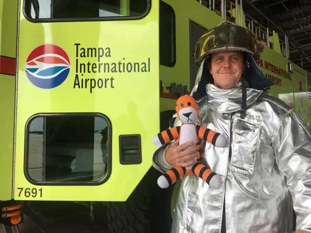 Bombeiro segura o tigre de pelúcia durante seu tour pelo aeroporto (Foto: Reprodução/Facebook/Tampa Internacional Airport)