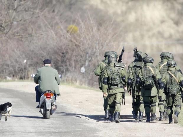 Homens armados que estariam a serviço da Rússia marcham do lado de fora de base militar ucraniana em Perevalnoye, na Crimeia (Foto: Vasily Fedosenko/Reuters)