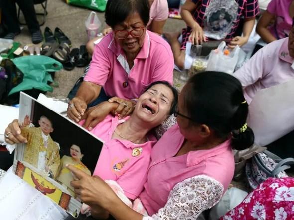 Mulher chora com uma foto do casal real da Tailândia na mão e é amparada por amigas em meio a um grupo acampado no hospital Siriraj, fazendo orações pelo rei Bhumibol Adulyadej, onde ele estava internado em Bangkok (Foto: Athit Perawongmetha/Reuters)