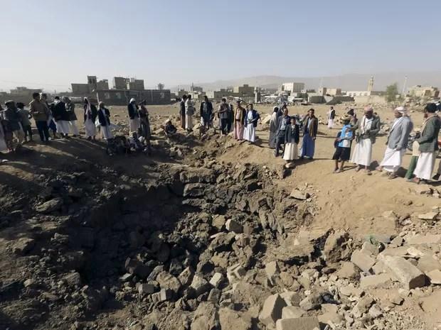 Moradores observam cratera aberta no solo por ataques (Foto: Khaled Abdullah/Reuters)