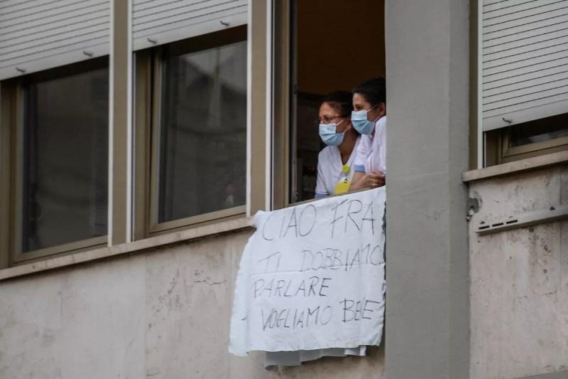 Enfermeiras da Policlínica Universitária Agostino Gemelli, em Roma, seguram faixa de adeus ao Papa Francisco, em 14 de julho de 2021, após o pontífice deixar o hospital onde passou por uma cirurgia no cólon.  — Foto: Filippo Monteforte/AFP