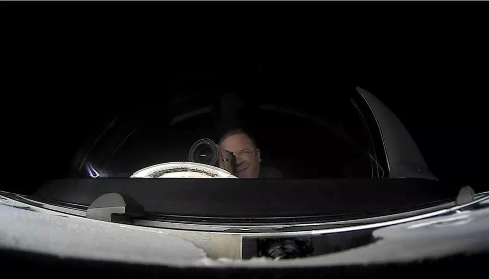 Chris Sembroski, tripulante da missão Inspiration4 fotografando a Terra através do domo da cápsula da SpaceX — Foto: Redes sociais/Inspiration4
