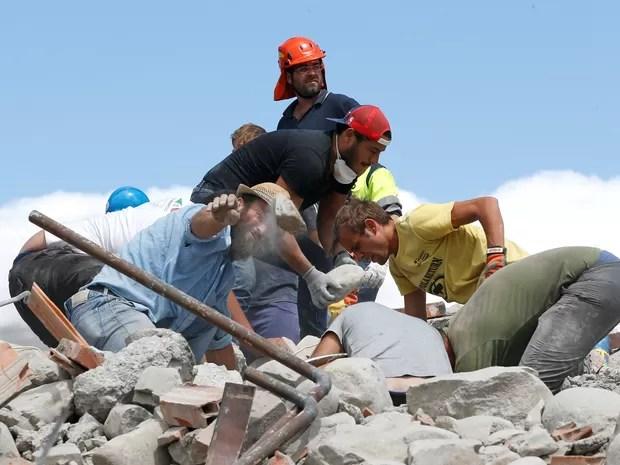 Socorristas usam as próprias mãos para retirar escombros e tentar alcançar vítimas na quarta-feira (24). Trabalhos de resgate prosseguem nesta quinta (Foto: Ciro De Luca/ Reuters)