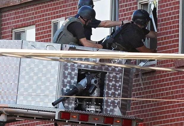 Policiais vasculham o apartamento do suspeito nesta sexta-feira (20) em Aurora, no estado americano do Colorado (Foto: AFP)