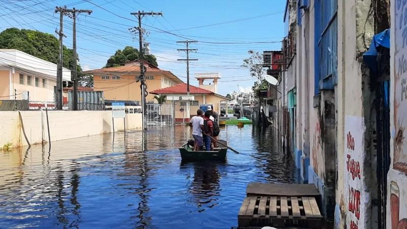 Trabalhadores usam canoas para passar pelo centro de Manaus, atingido pelo cheia do Rio Negro — Foto: Eliana Nascimento/G1