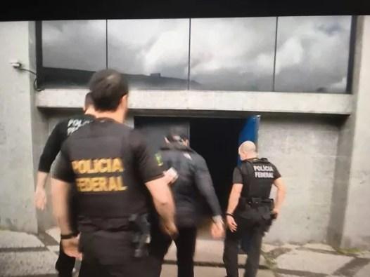 Mantega, de casaco preto e boné, chega à sede da PF em São Paulo (Foto: Reprodução/GloboNews)