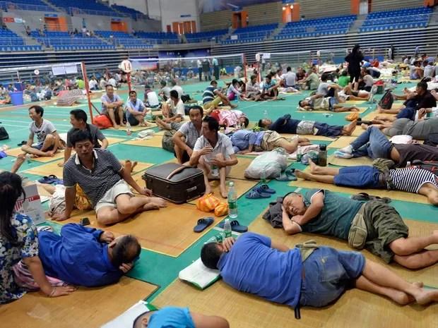Trabalhadores chineses são levados para um ginásio em Guangzhou, sul da China, por causa da chegado do tufão Nida (Foto: STR / AFP Photo)