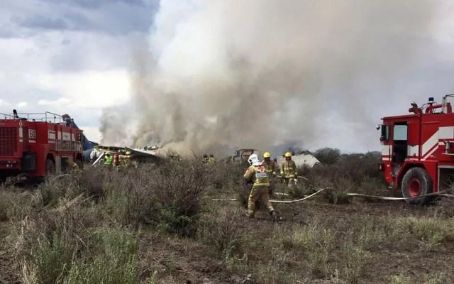 Bombeiros apagam fogo após acidente com avião da Aeroméxico perto do aeroporto de Durango, no México, na terça-feira (31) (Foto: Civil Defense Office of Durango Photo via AP)