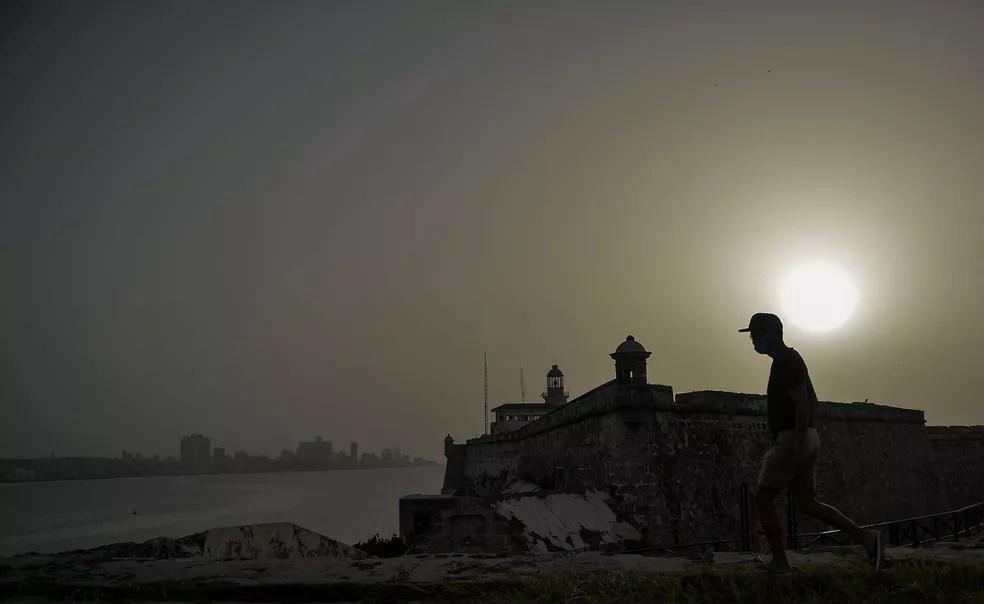 Homem caminha perto do Castelo de Morro enquanto nuvem de poeira do Saara encobre a cidade de Havana, em Cuba, na quarta-feira (24)  — Foto: Yamil Lage / AFP