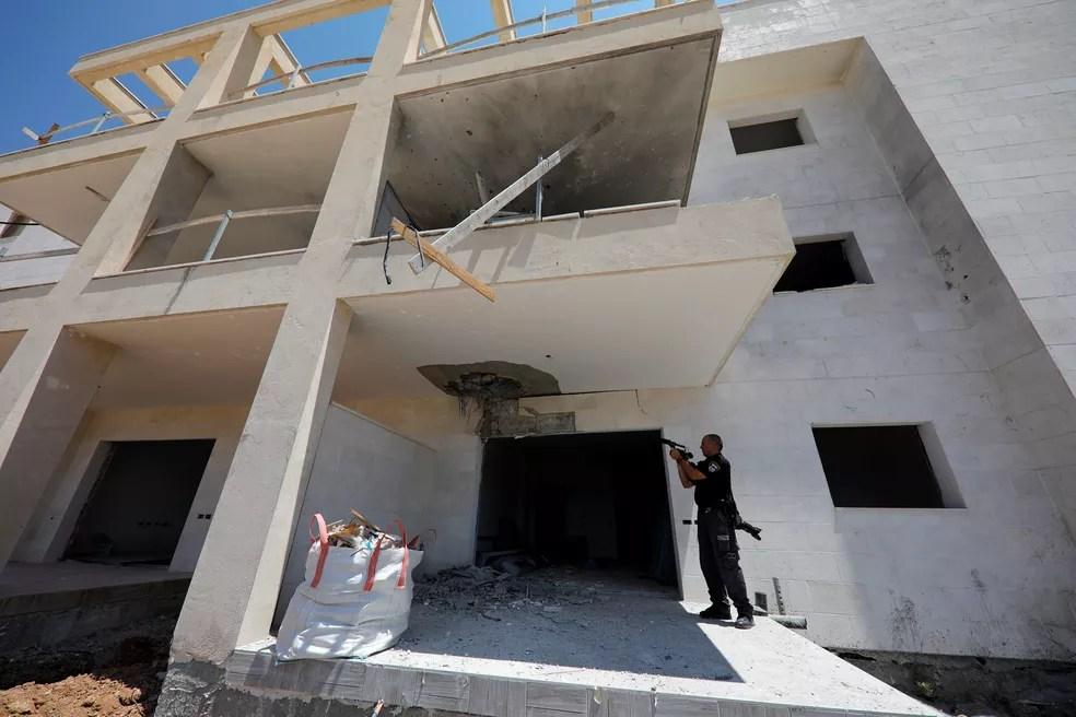 Policial israelense mostra dano causado por foguete palestino em construção na cidade de Sderot (Foto: Amir Cohen/Reuters)