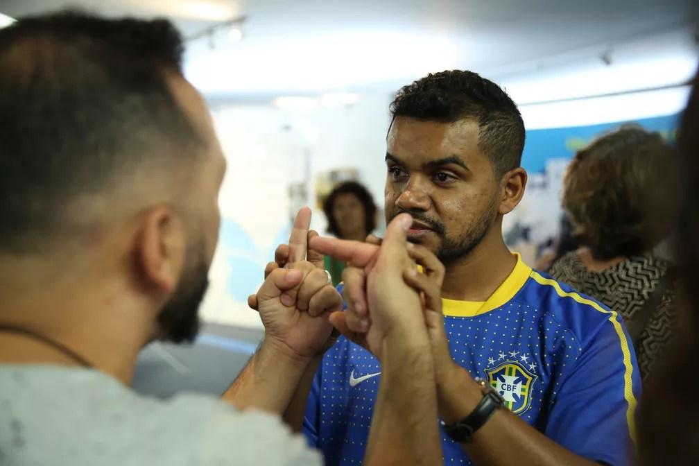 Carlinhos com camisa do Brasil e o interprete Hélio aguardam início do jogo da seleção (Foto: Marcelo Brandt/G1)