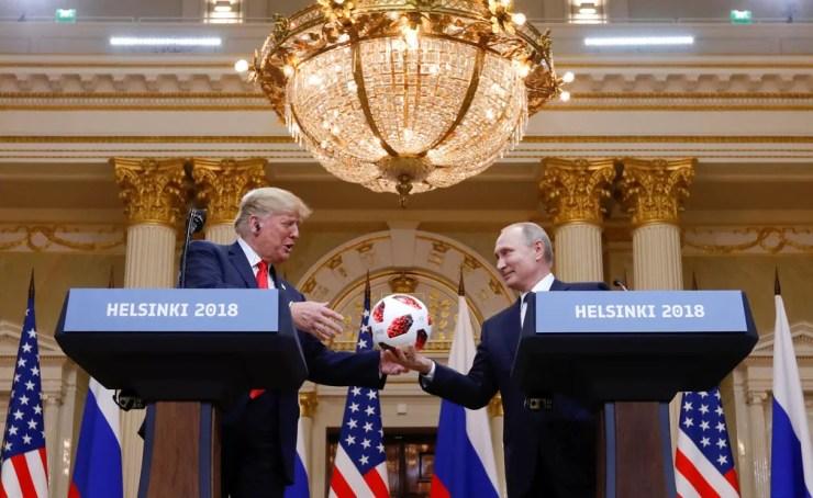 Presidente dos EUA, Donald Trump, recebe uma bola oficial da Copa de Vladimir Putin, durante encontro em Helsinque, na Filândia, nesta segunda-feira (16) (Foto: Kevin Lamarque/ Reuters)