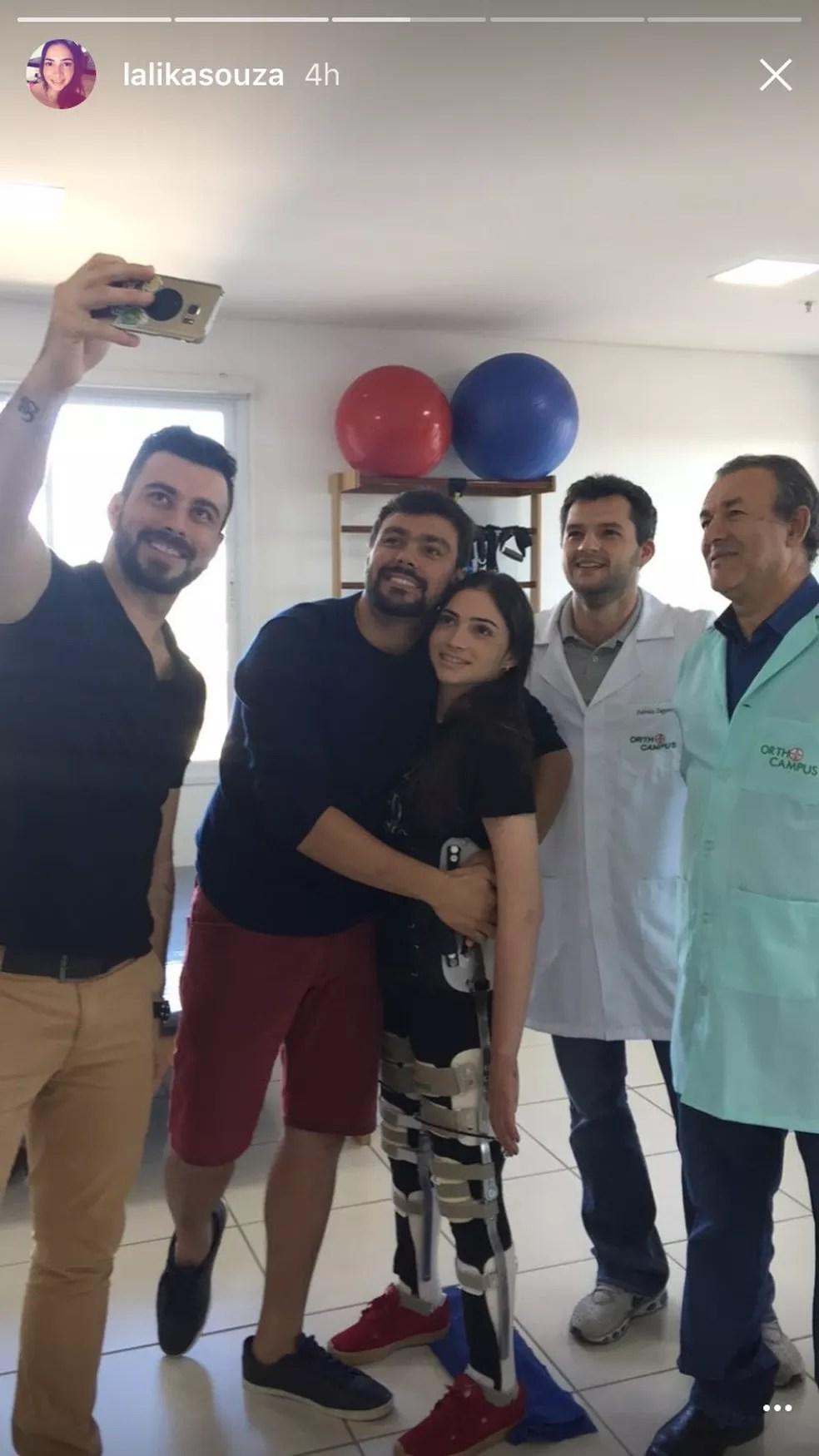 Lais Souza fica em pé com a ajuda de aparelho e posa para foto a equipe que cuida da sua reabilitação (Foto: Reprodução Instagram)