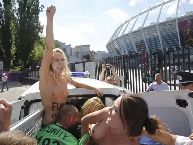 Ativistas nuas do grupo Femen são detidas após manifestação contra prostituição feminina em frente ao Estádio Olímpico de Kiev, na Ucrânia, neste domingo (24) (Foto: Gleb Garanich/Reuters)