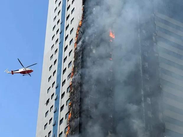 Helicóptero sobrevoa prédio em chamas em Sharjah, nos Emirados Árabes Unidos, na quinta (1º) (Foto: AP Photo)
