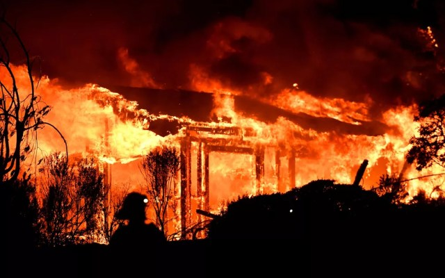 Bombeiros combatem incêndio em uma casa em Napa, na Califórnia, na segunda-feira (9) (Foto: Josh Edelson/AFP)