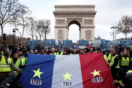 Manifestantes carregam a bandeira francesa com as datas que marcaram a história do país acrescentando 2018 por causa dos protestos contra o governo Macron durante manifestação na Champs Elysees, perto do Arco do Triunfo — Foto: Benoit Tessier/Reuters
