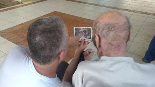 Michel e Juan relembram o passado por meio de fotografias (Foto: Matheus Fazolin/G1)