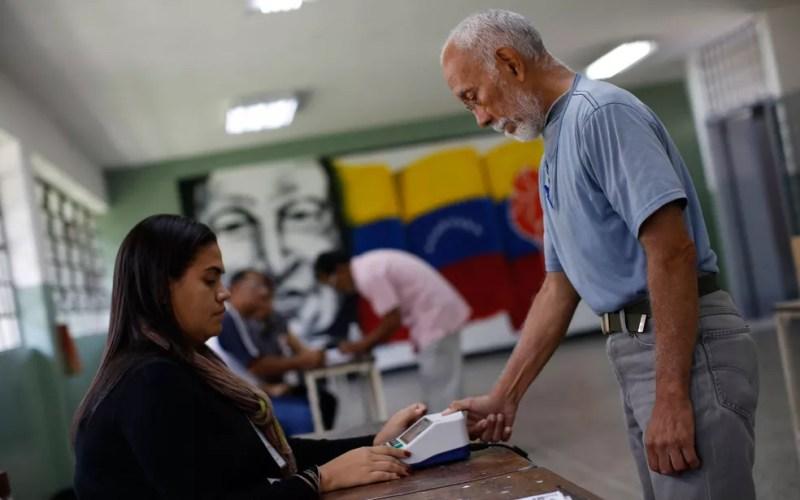 Eleitor se identifica antes de votar para a Assembleia Constituinte em Caracas, na Venezuela, no domingo (30) (Foto: Reuters/Carlos Garcia Rawlins)