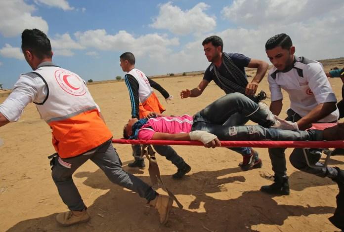 Palestino ferido em confronto na fronteira da Faixa de Gaza com Israel nesta segunda-feira (14) é transportado (Foto: Said Khatib/AFP)