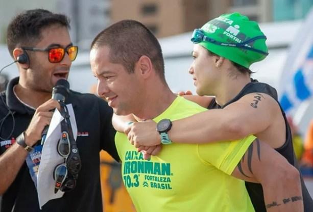 Márcio carrega Dani nas costas minutos antes da largada do Meio Ironman — Foto: Elton Viana