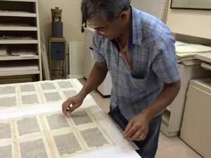 Livro é recuperado por restaurador, após ser retirado de máquina onde ele recebe uma polpa feita de celulose para recuperar espaços danificados por traças. (Foto: Cristina Boeckel/ G1)