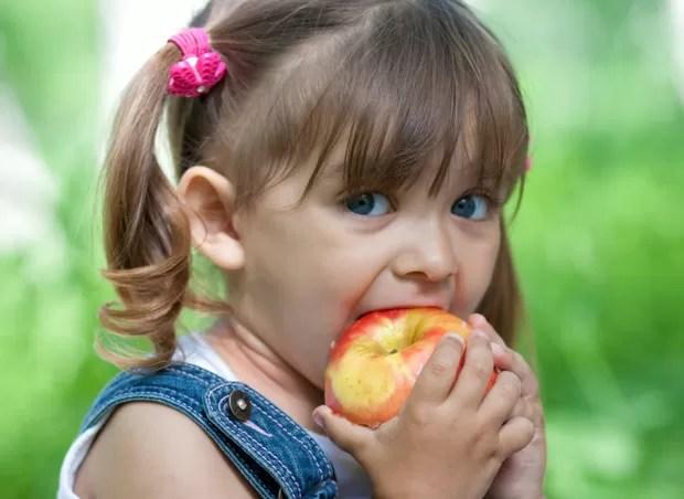 Criança comendo maçã (Foto: Shutterstock)