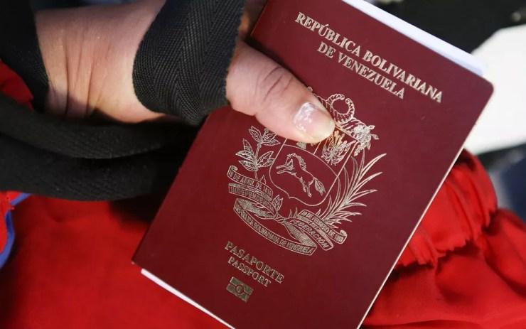 Venezuelana exibe passaporte em aeroporto em Lima, no Peru, antes de embarcar com destino à Venezuela, em imagem de arquivo — Foto: Teo Bizca/AFP