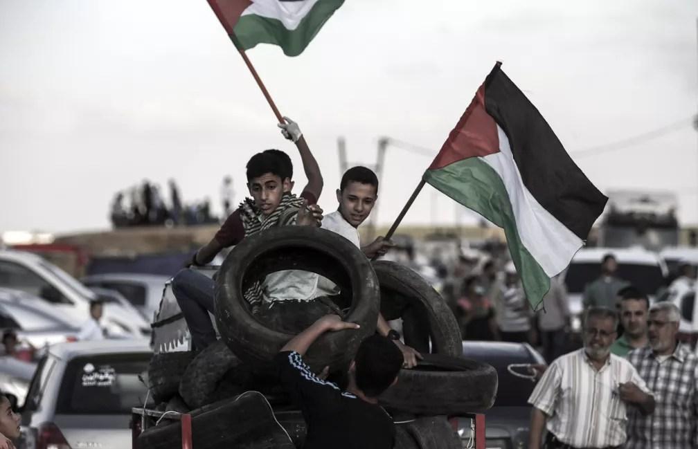 Jovens palestinos carregam pneus e bandeiras nesta sexta-feira (29) para participar de protesto na fronteira da Faixa de Gaza (Foto: Mahmud Hams/AFP)