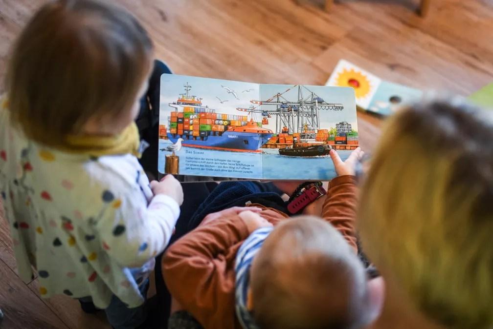 Professora lê livros com duas crianças em creche em Recklinghausen, oeste da Alemanha, no dia 24 de fevereiro. — Foto: Ina Fassbender/AFP