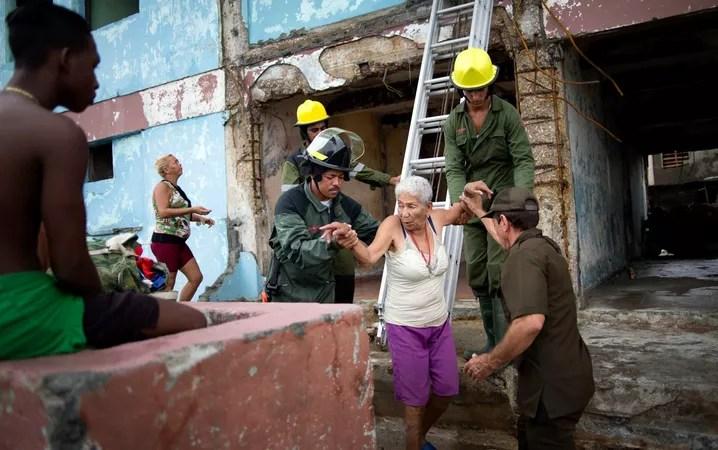 Bombeiros ajudam uma senhora a recuperar algumas roupas de sua casa que foi destruída pelo furacão Matthew em Baracoa, Cuba