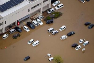 Veículos estão embaixo d'água em Marumori, província japonesa de Miyagi, nesta segunda-feira (14), após a passagem do furacão Hagibis — Foto: Notícias Kyodo via AP