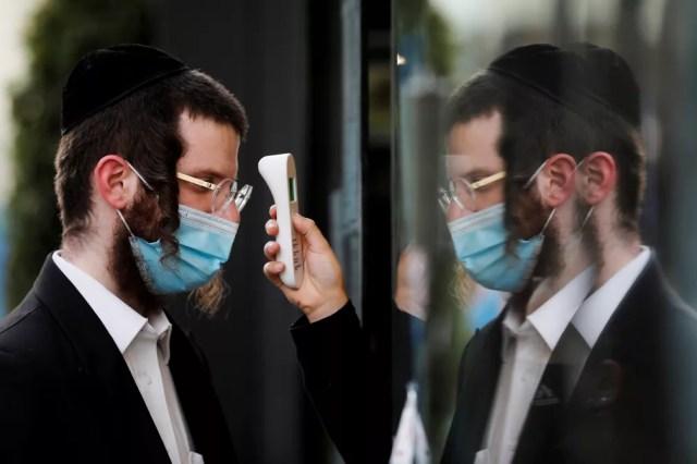 Homem tem a temperatura checada ao entrar em shopping de Ashdod, Israel, em 5 de maio — Foto: Amir Cohen/Arquivo/Reuters