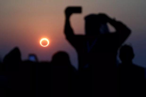 Pessoas tiram fotos com seus smartphones enquanto monitoram o eclipse solar anular na Arábia Saudita — Foto: REUTERS/Hamad I Mohammed