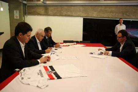 Marcio Aith (direita) e presidente Leco (ao centro na esquerda) assinam contrato com patrocínio máster (Foto: Igor Amorim / saopaulofc.net)