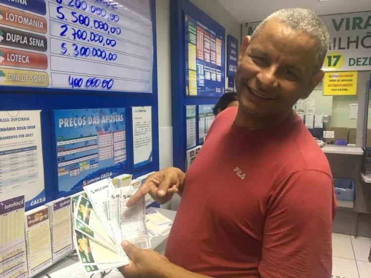 O aposentado Cleumar Webert, de 53 anos, expondo os jogos que irá fazer apostar na Mega da Virada — Foto: Hamanda Viana/G1