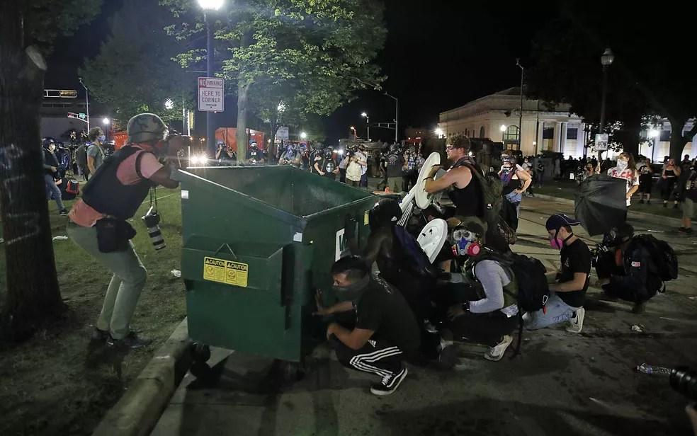 Manifestantes se protegem atrás de uma lixeira em Kenosha, Wisconsin, enquanto a polícia atira gás lacrimogênio — Foto: Kamil Krzaczynski / AFP Photo