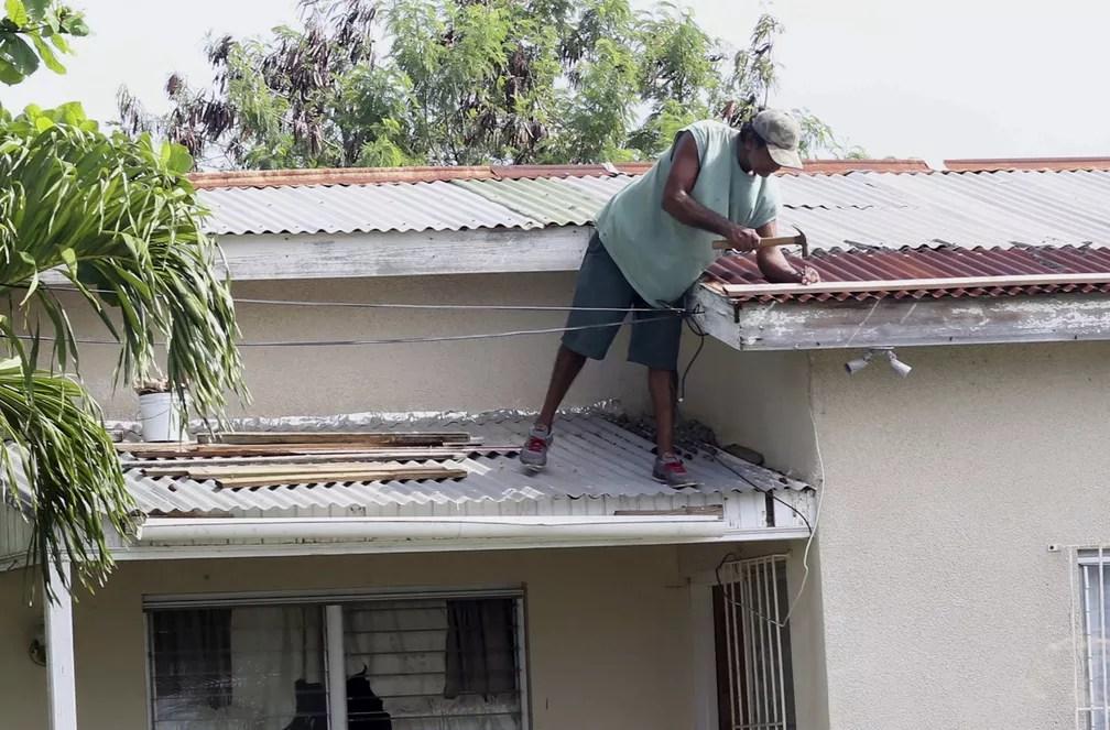 Homem faz pequenos reparos em telhado de casa antes da passagem do furacão Irma em  St. John's, Antigua e Barbuda (Foto: AP Foto/Johnny Jno-Baptiste)