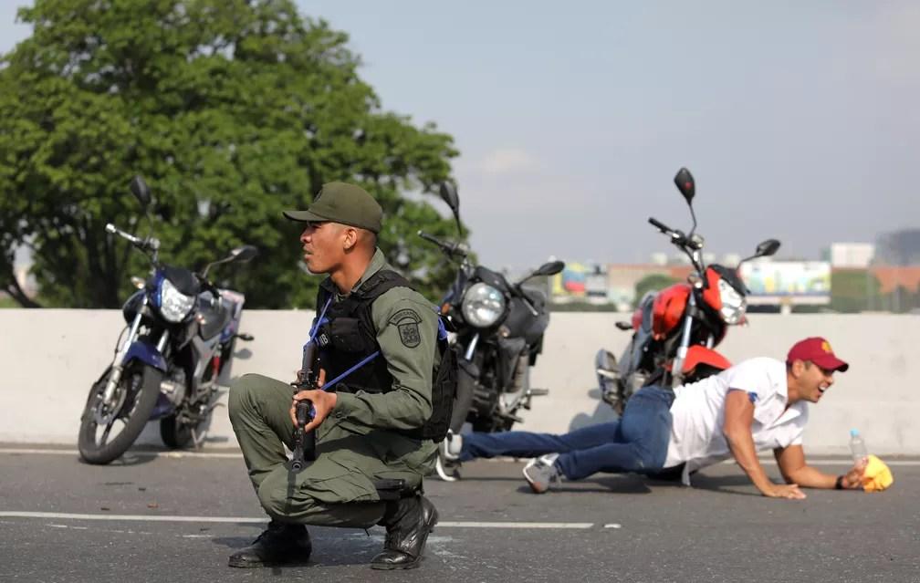 Um militar e um civil se protegem perto da base aérea conhecida como 'La Carlota', em Caracas — Foto: Manaure Quintero/Reuters