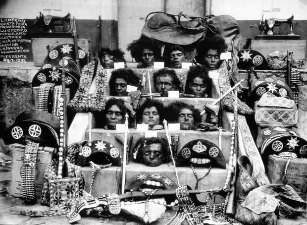 Fotografia icônica mostra as cabeças de Lampião (última de baixo), Maria Bonita (logo acima de Lampião) e outros cangaceiros do bando. No canto esquerdo superior, uma placa lista os nomes e indica a data em que eles foram mortos (Foto: Reprodução de 'Ciclo do Cangaço: Memórias da Bahia', de José Castro/Autor desconhecido/Wikipedia)