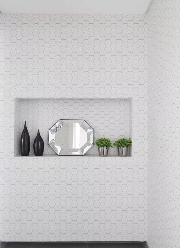 HALL | O papel de parede cinza em hexágono da Housed é a primeira coisa que os convidados do casal virão, trazendo charme e convidando a todos para conhecer o apê junto com os objetos decorativos da Zacche Home. (Foto: Mariana Orsi/ Divulgação)