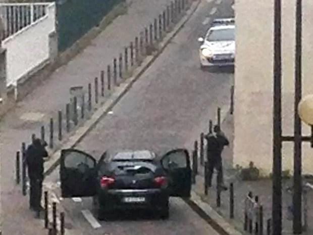 Homens armados são vistos saindo de um carro e apontando armas a um carro da polícia perto do escritório da revista satírica 'Charlie Hebdo', em Paris (Foto: Anne Gelbard/AFP)