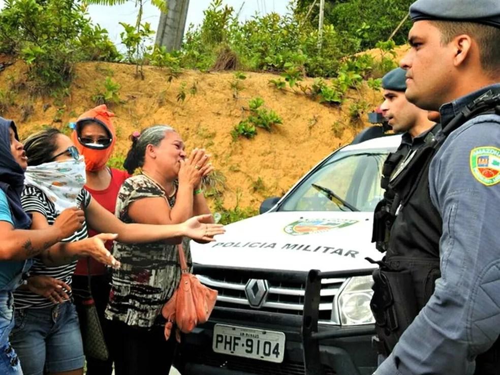 Familiares de presos cobrem rostos e pedem informações de policiais sobre mortes em presídio em ManausManaus ( (Foto: Isis Capistrano / G1 AM)