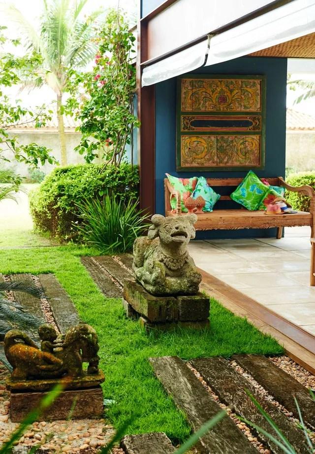 Painel de madeira e escultura, ambos da Afranio, e banco rústico de madeira compõe o décor da varanda   (Foto: Thiago Justo)