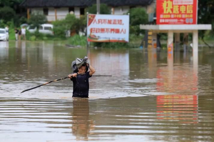 Homem carrega pertences enquanto anda por rua inundada em Guangxi, na China, neste domingo (9). — Foto: Stringer/Reuters