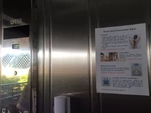 Dicas para economizar água foram coladas nos elevadores do prédio (Foto: Matheus Rodrigues/ G1)