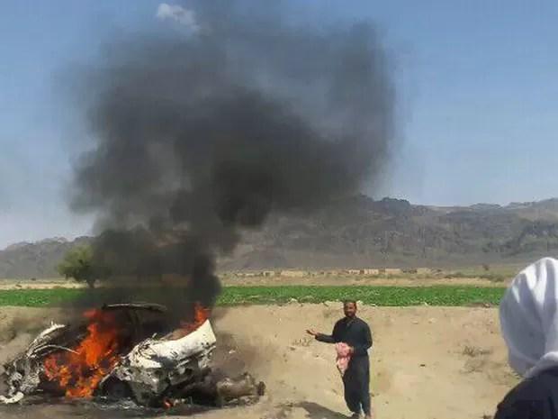 Fotografia feita no sábado mostra moradores paquistaneses  em volta de um veículo destruído por um drone, no qual o líder Akhtar Mansour estaria. (Foto: AFP)